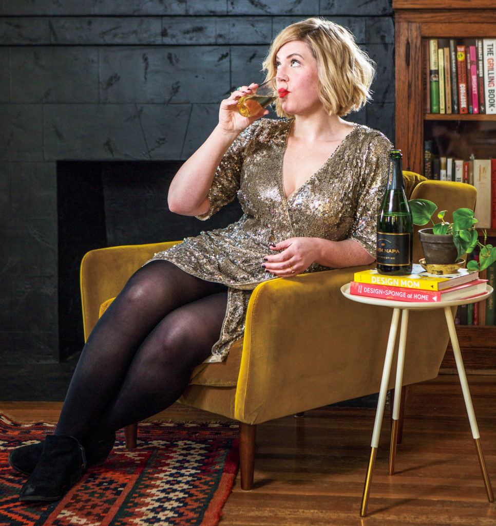 Blonde woman Emily Farris in sequined dress drinking champagne.