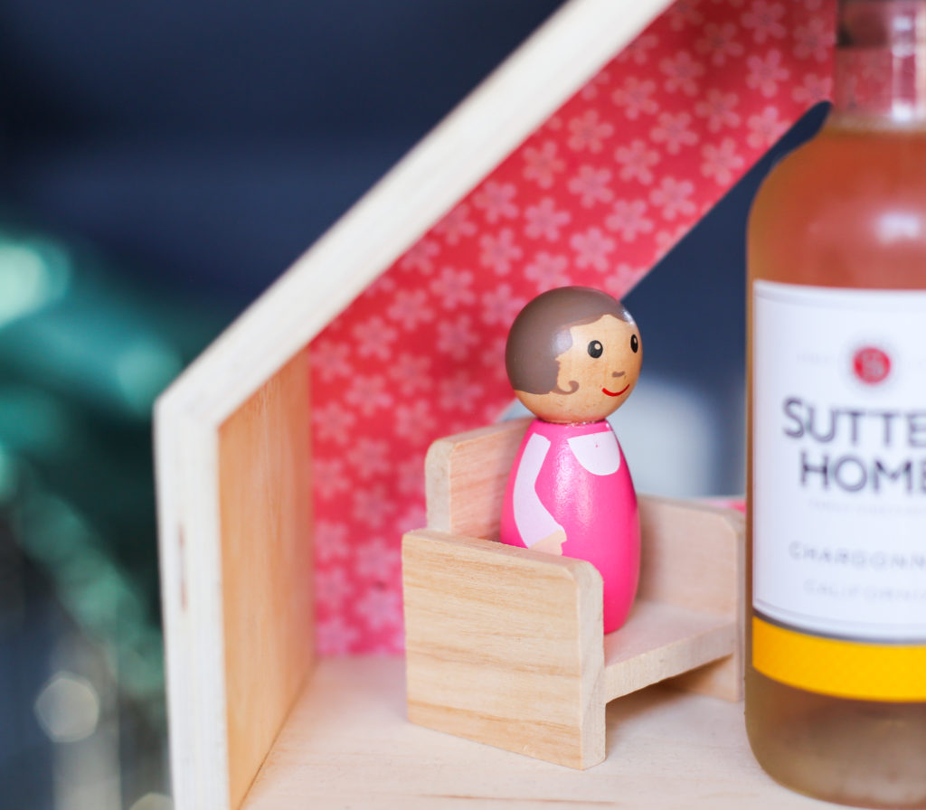 Wooden dollhouse mother looking at bottle of wine