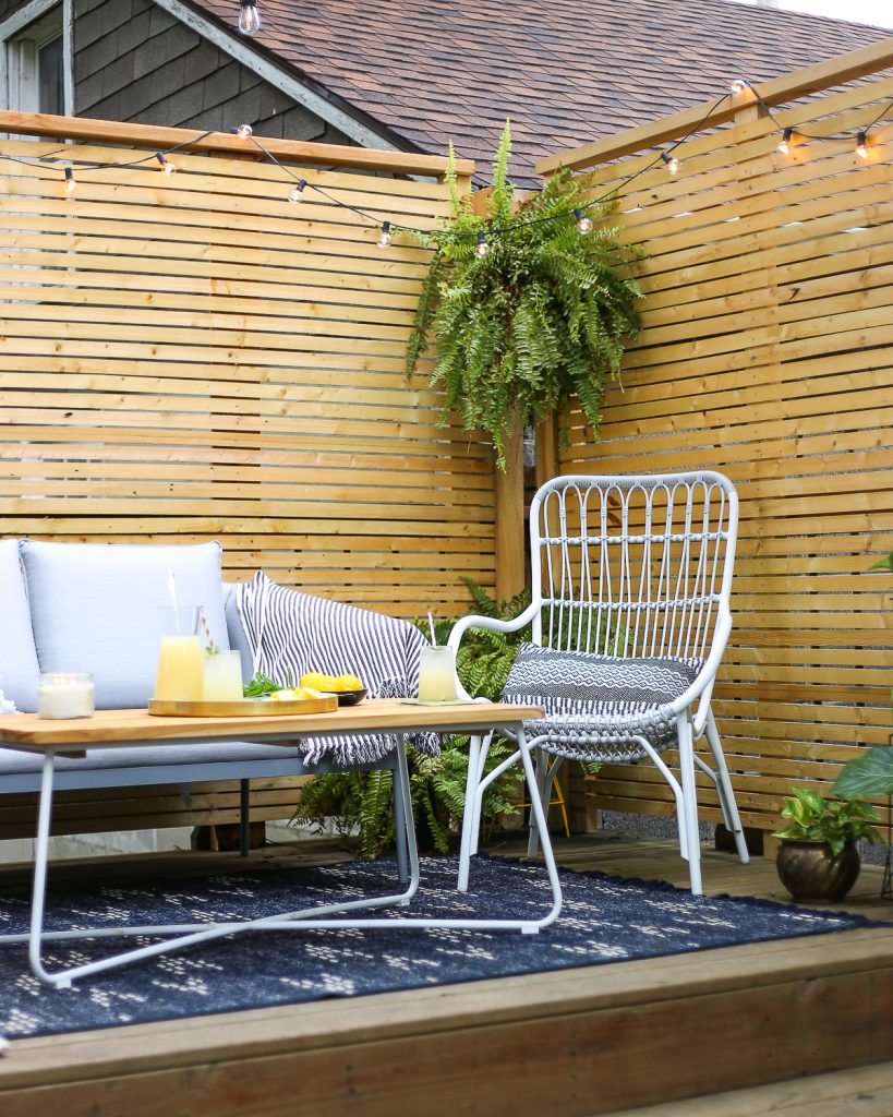 Modern patio furniture on a back deck with a slatted-wood privacy screen