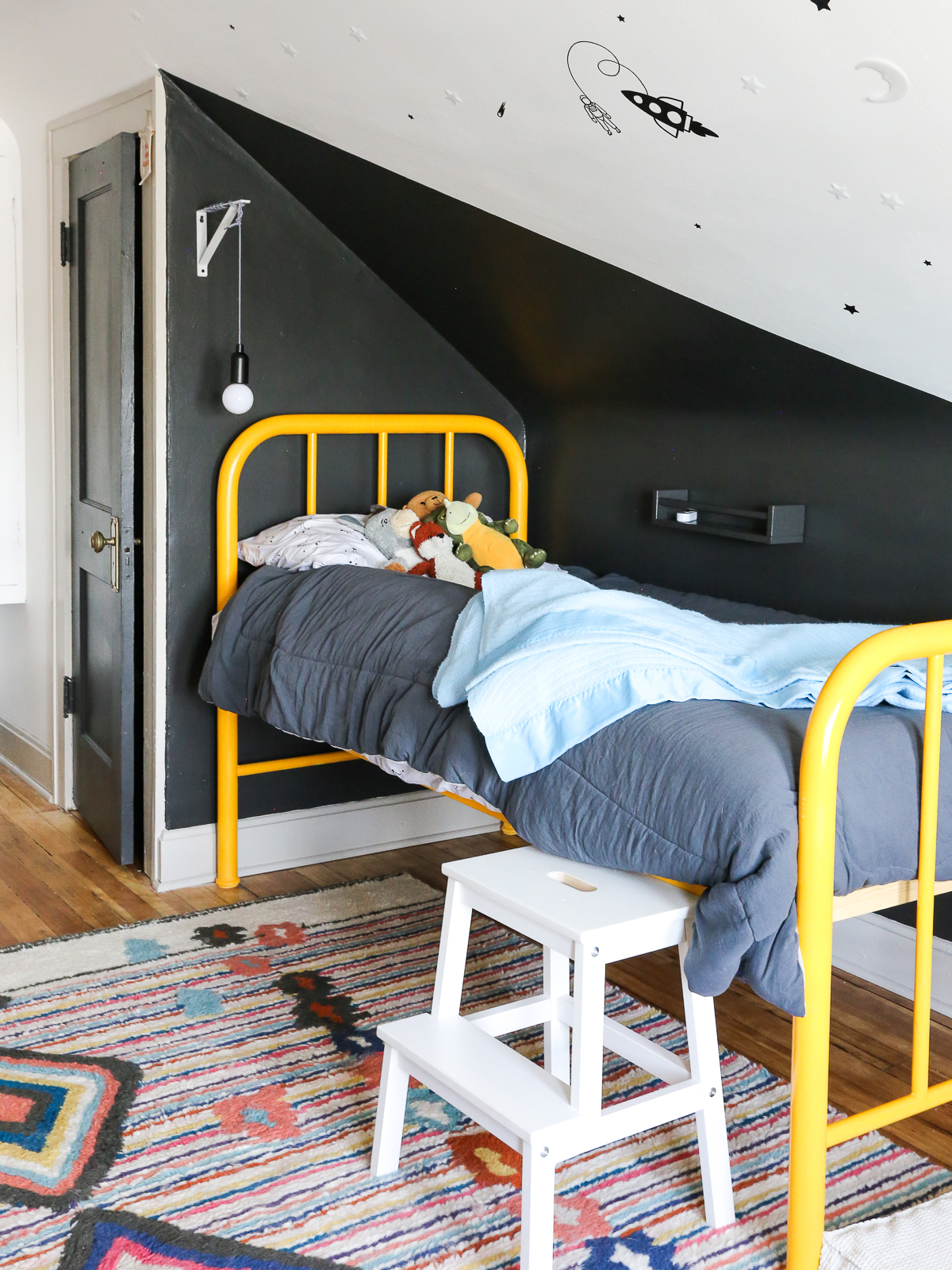toddler room renovation reveal with wood floors, wool rug, and yellow metal bed