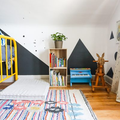 toddler room with wood floors, wool rug, and yellow metal bed