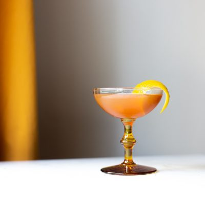 lemon vanilla old fashioned cocktail in a coupe glass with an amber stem and a lemon twist garnish