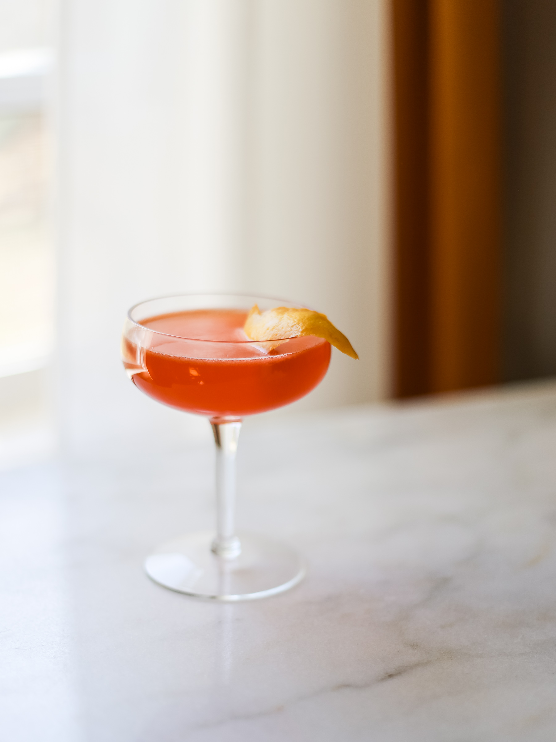 reddish-orange cocktail in a coupe glass